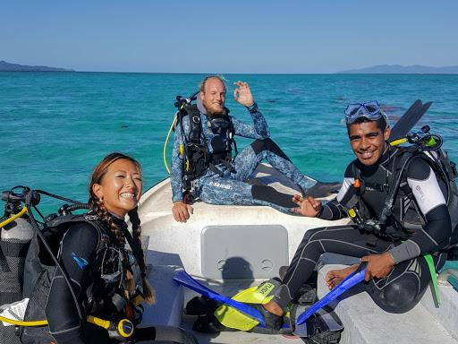 People smiling in scuba diving gear on a boat in the sea